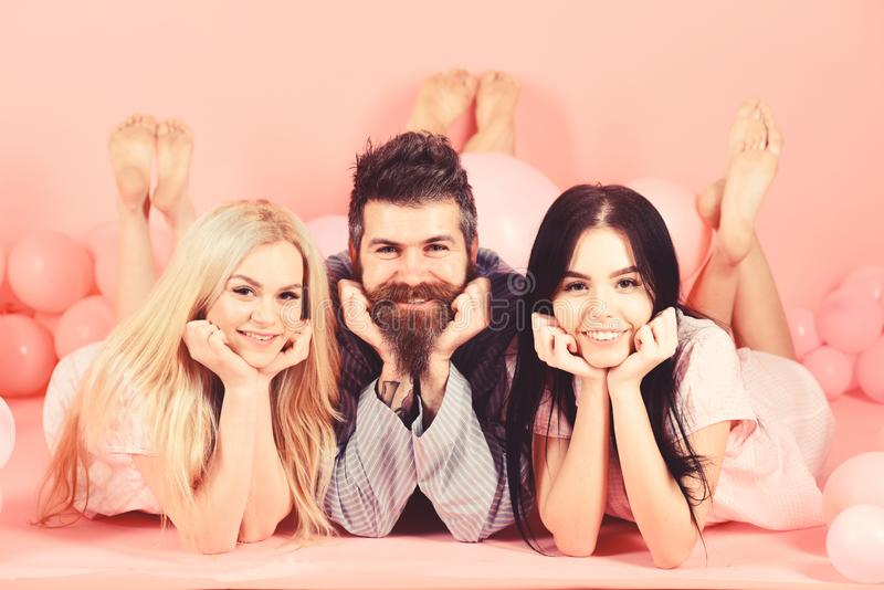 Girls fall in love with bearded macho, pink background. Alpha male concept. Man with beard and mustache attracts blonde. And brunette girls. Threesome on stock image