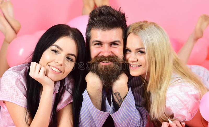 Girls fall in love with bearded macho, pink background. Threesome on smiling faces lay near balloons. Alpha male concept. Man with beard and mustache attracts royalty free stock image