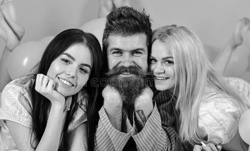 Girls fall in love with bearded macho, pink background. Threesome on smiling faces lay near balloons. Alpha male concept. Man with beard and mustache attracts royalty free stock images