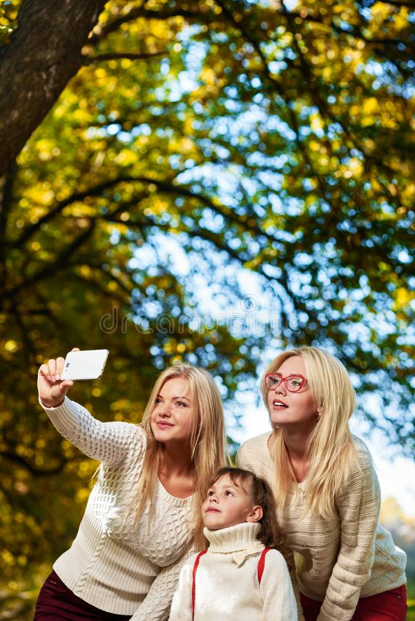 Girls Family selfie in park. Beautiful girls with little sisters making selfie in park royalty free stock image