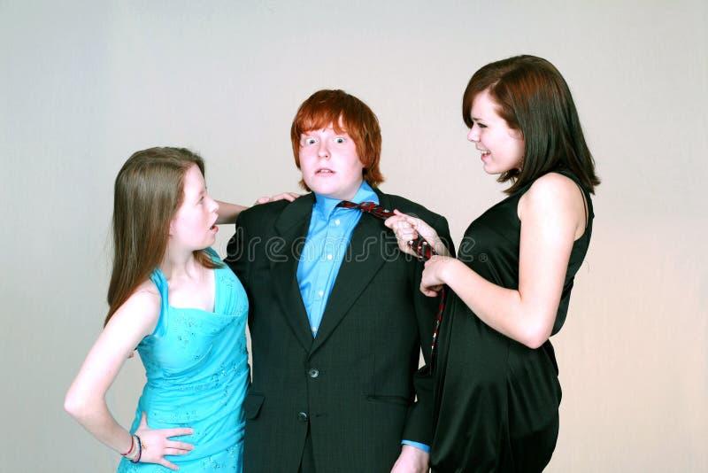 Girls Fighting Over Blushing Boy Royalty Free Stock Images