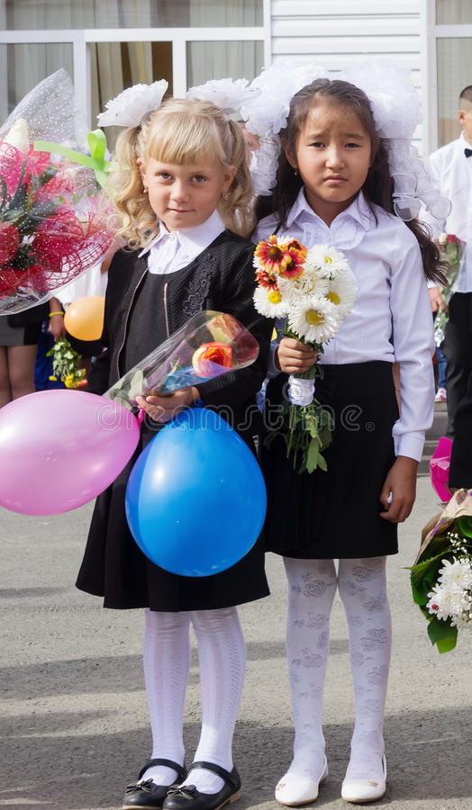 Girls-first-grader at the school on September 1 lineup royalty free stock photo