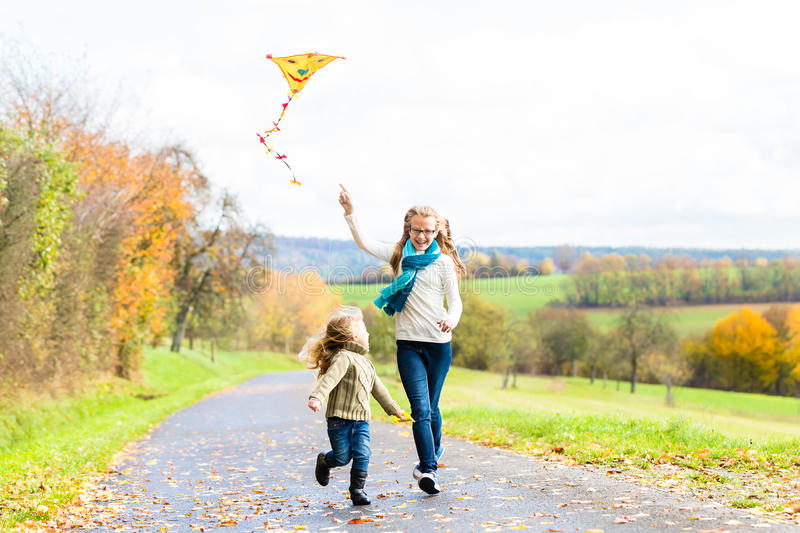 Girls fly an kite on autumn or fall meadow. Girls running together with kite on autumn or fall meadow royalty free stock photography