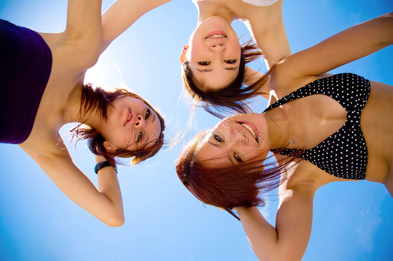 Girls friend having fun under sunny blue sky. Three girls friend having fun under sunny blue sky on summer time royalty free stock photo