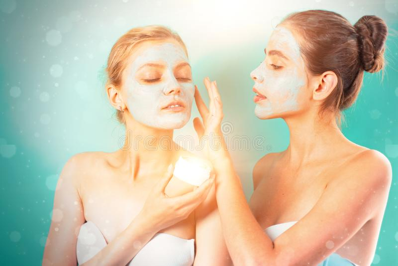 Girls friends making clay facial mask. Anti age mask. Stay beautiful. Skin care for all ages. Women having fun cucumber. Skin mask. Pure beauty. Beauty product stock image