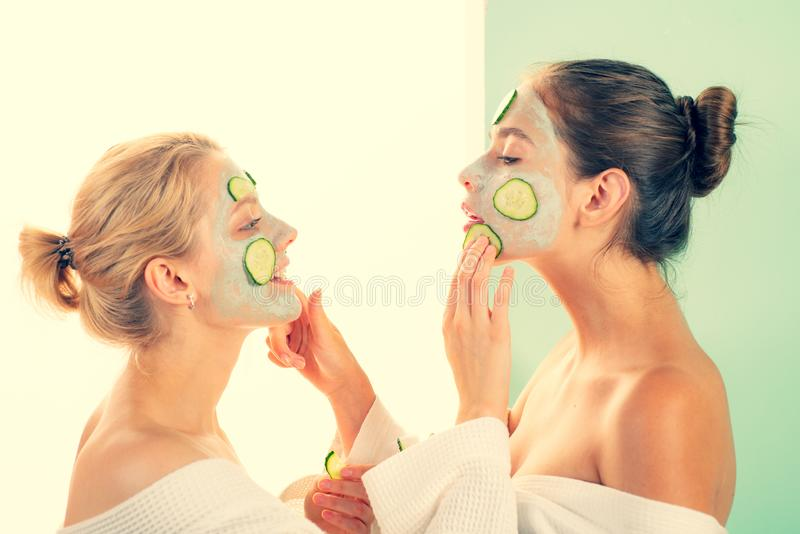 Girls friends sisters in bathrobes making clay facial mask. Anti age care. Stay beautiful. Skin care for all ages. Women royalty free stock images