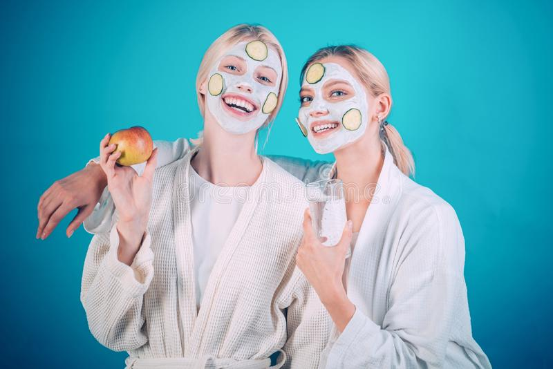 Girls friends sisters making clay facial mask. Anti age mask. Stay beautiful. Skin care for all ages. Women having fun. Cucumber skin mask. Drink water eat royalty free stock images