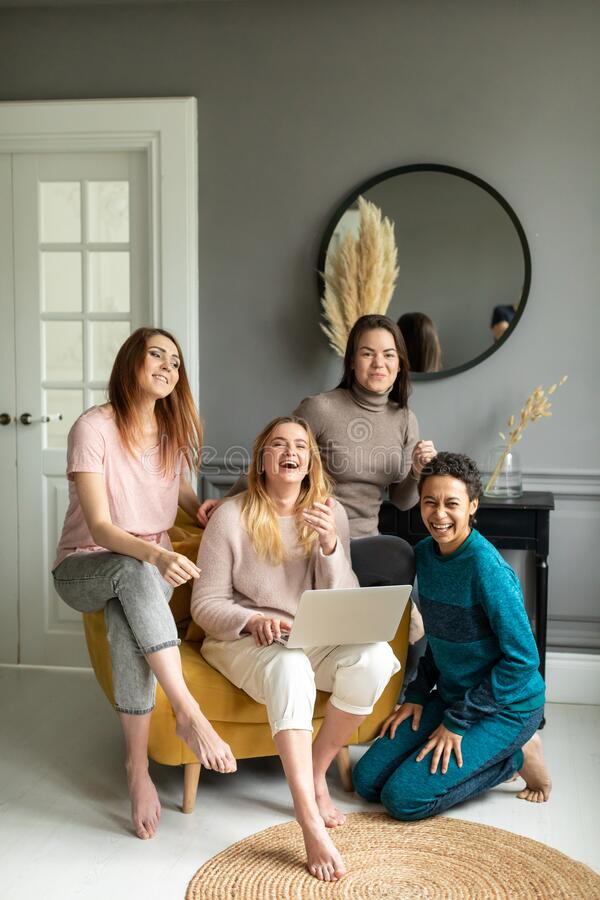 Girls Friendship Online Shopping Concept. four beautiful friends sit at home and order over the Internet. High quality photo stock images