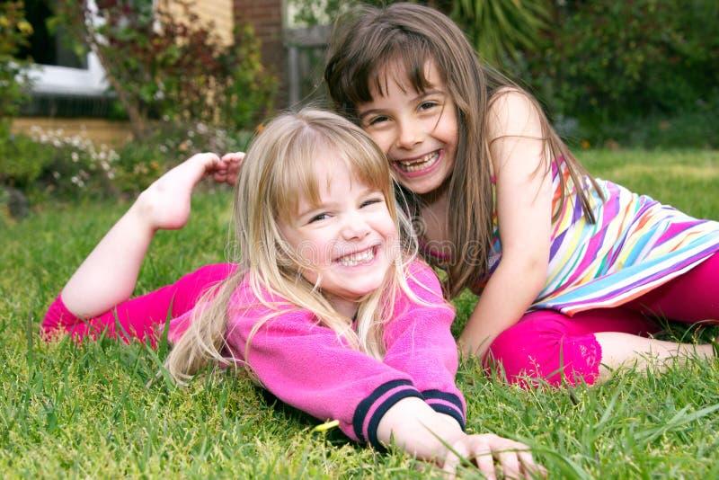Girls in garden. Two happy little girls having fun in the garden stock image