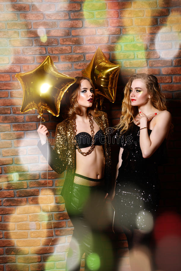 Girls with golden balloons. Two glamorous girls at a night party. Beauty, fashion. Entertainment stock photography
