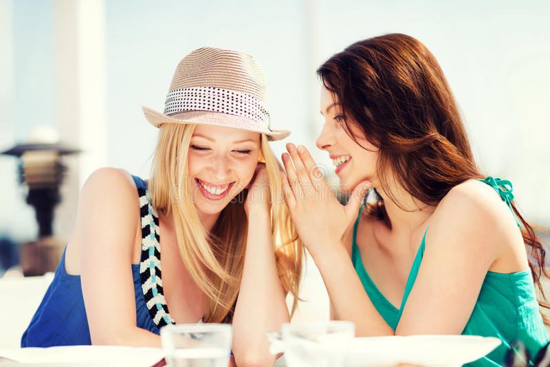 Girls gossiping in cafe on the beach. Summer holidays and vacation - girls gossiping in cafe on the beach royalty free stock photography