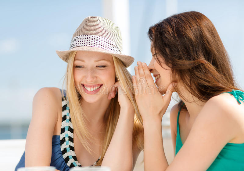 Girls gossiping in cafe on the beach. Summer holidays and vacation concept - girls gossiping in cafe on the beach stock photos