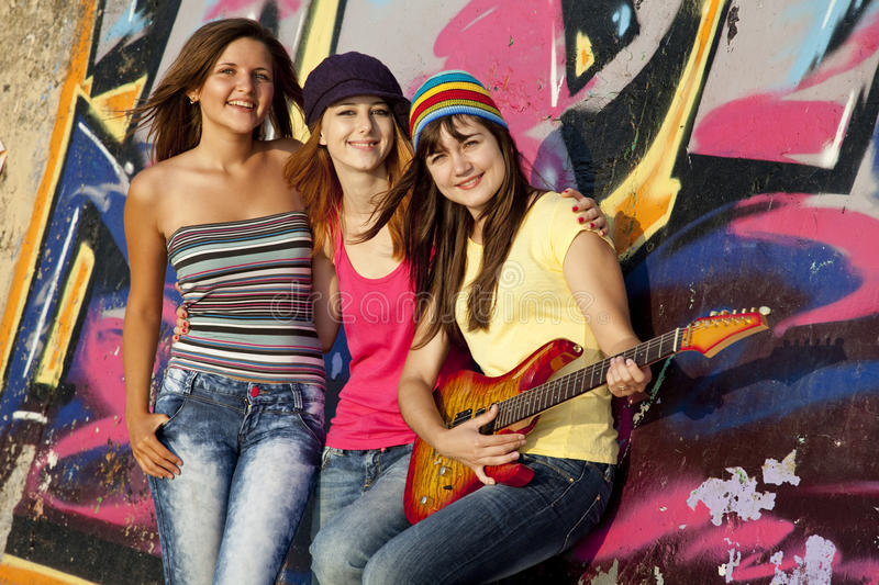 Girls with guitar and graffiti wall