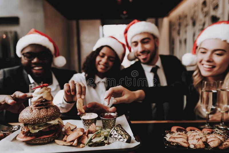 Girls and Guys. Burger. Santa`s Hat. Young People. royalty free stock photos