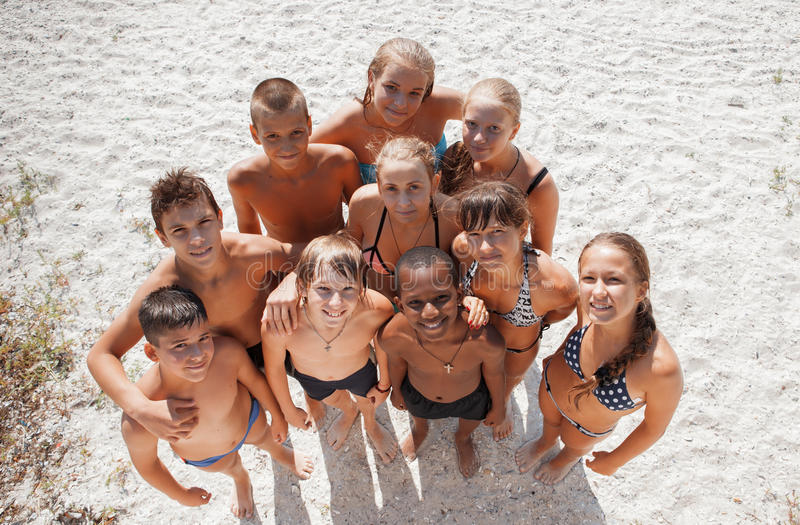 Girls and guys on sand on summer vacation royalty free stock photo