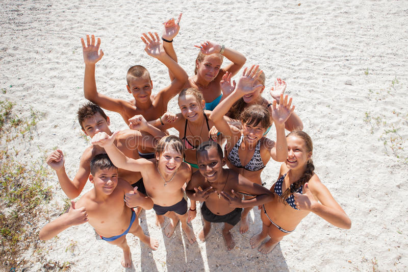 Girls and guys on sand on summer vacation royalty free stock image