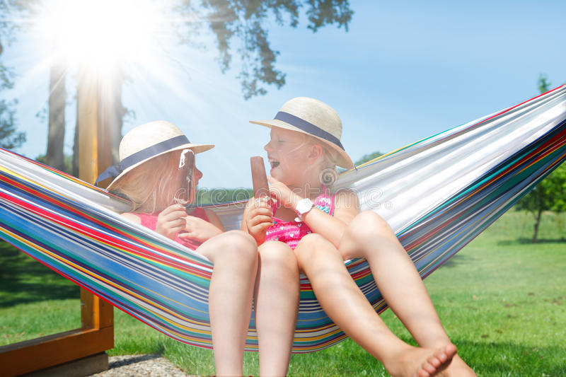 Girls in hammock eating ice cream royalty free stock photography