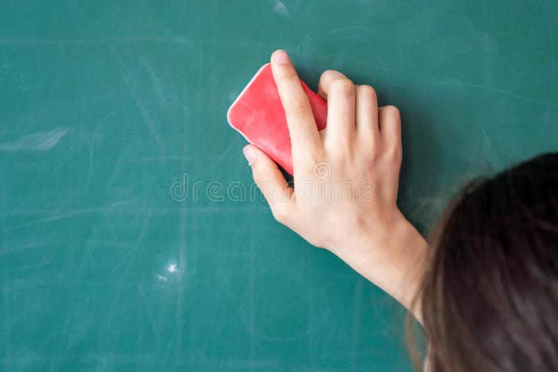 Girls hand in elementary school cleaning board with sponge stock photos