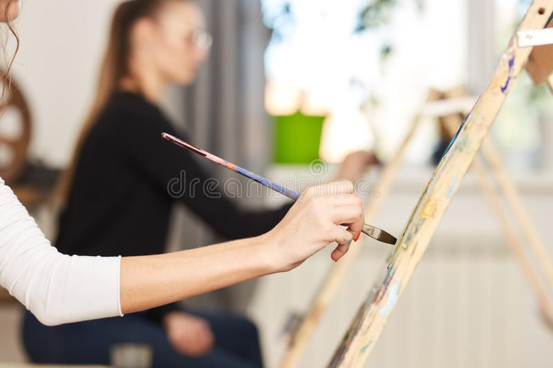 Girls hand holds a paint brush. Process of painting picture at the easels in the art studio.  royalty free stock images