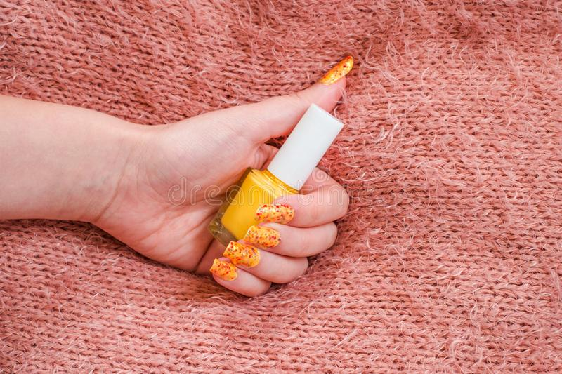 Girls hand with nailart on sweater  and a Bottle of nail polish. Close view royalty free stock photo
