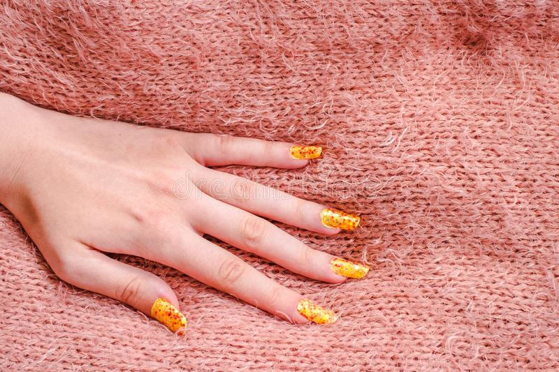 Girls hand with nailart on sweater. Close view stock image