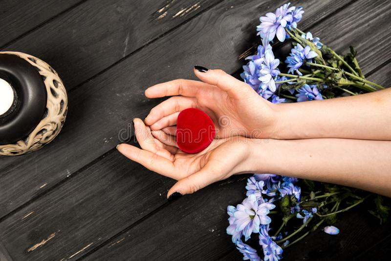 Girls hands holding flower petals. Hands of girl holding red petals with flowers on wooden table in background stock photography