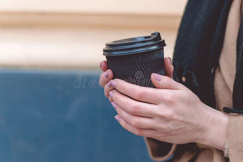 Close up of women hands holding paper cup of coffee on natural morning background royalty free stock images