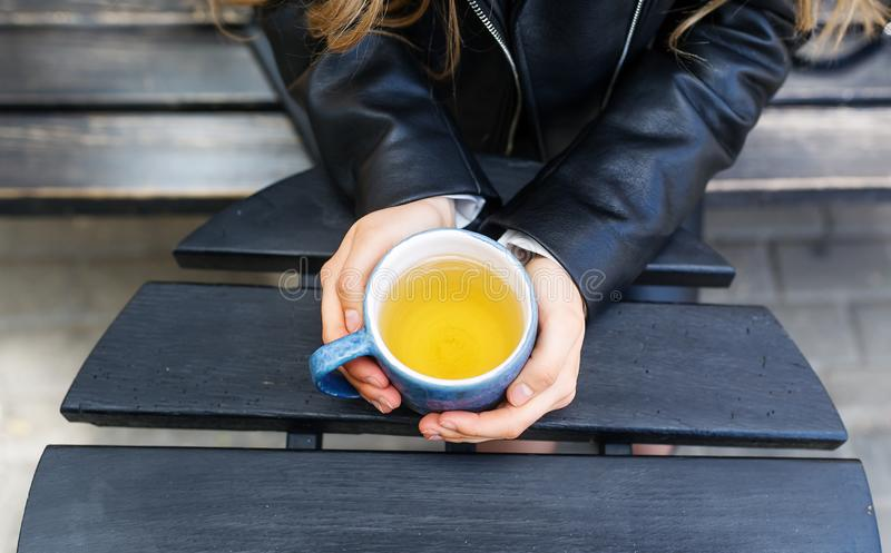 Girls hands holding tea cup. Top view royalty free stock photography