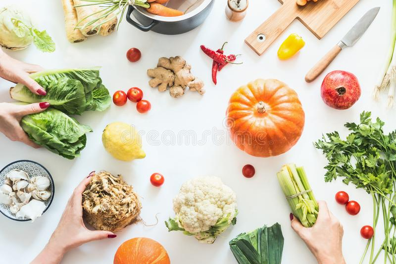 Girls hands holding various seasonal vegetables on white background with pumpkins, pot, cutting board and knife, top view. stock photos