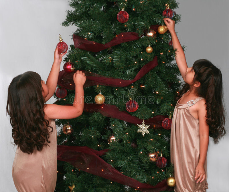 Girls hanging ornaments on Christmas tree stock images