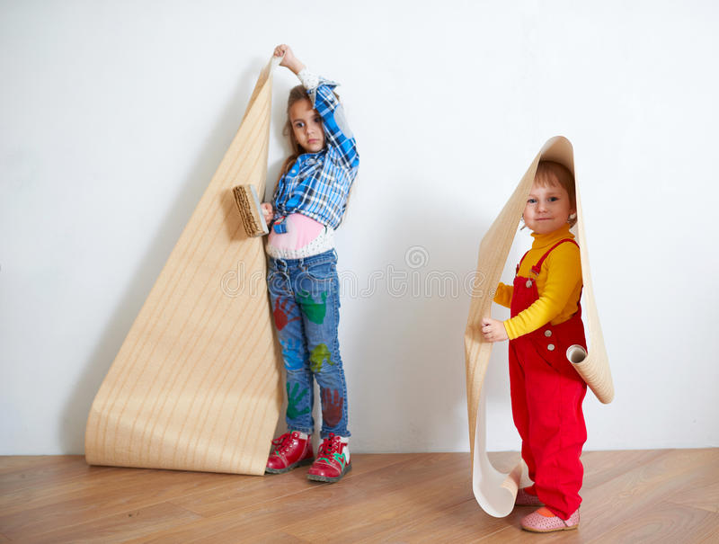 Girls hanging wallpaper. Decorating the wall. Cute little girls hanging wallpaper. Decorating the wall royalty free stock photo