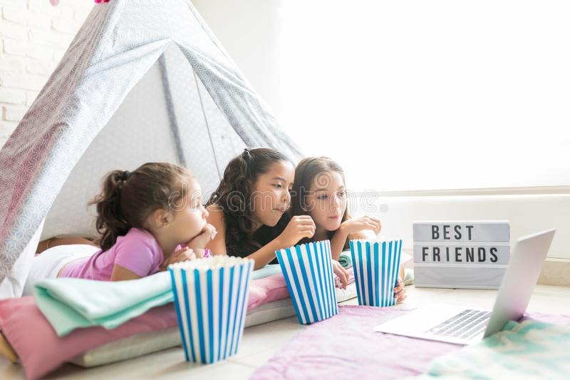 Girls Having Popcorns While Watching Movie On Laptop In Tipi. Tent during pajama party stock images