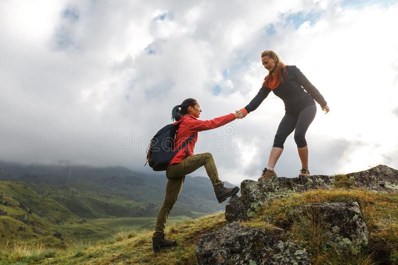 Girls helping each other hike up a mountain at sunrise. Giving a. Young Girls helping each other hike up a mountain at sunrise. Giving a helping hand, and active royalty free stock images