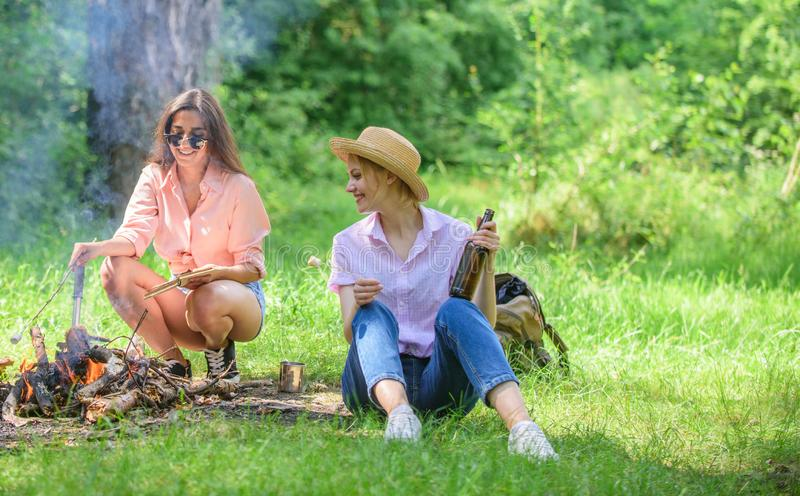 Girls hikers camping forest roasting marshmallows. Roasting marshmallows popular group activity around bonfire. Couple royalty free stock image