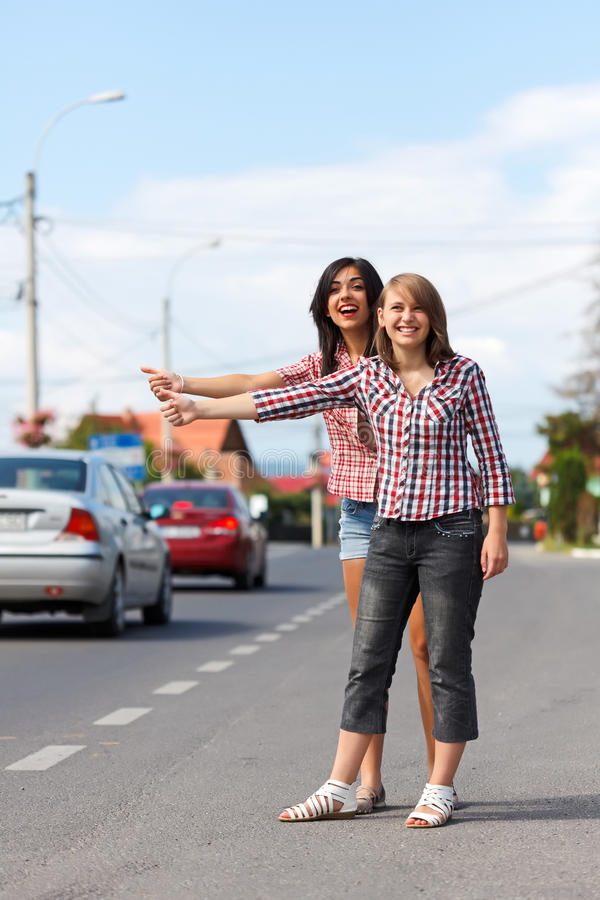 Girls hitch-hiking. Two hopeful girls hitch-hiking on a roadside stock photography
