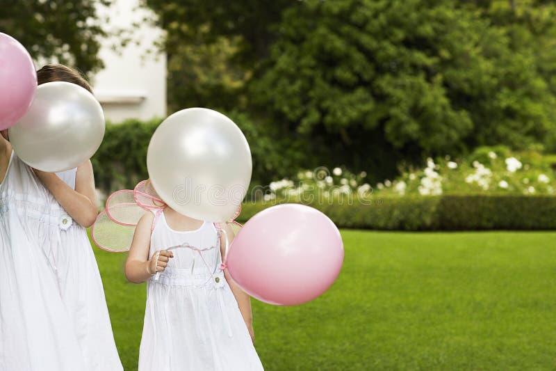 Girls Holding Balloons In Garden stock image