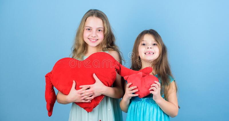 Girls hug red plush heart toy symbol love. Sisterhood concept. Valentines day. Friendly relations siblings. Family love royalty free stock image