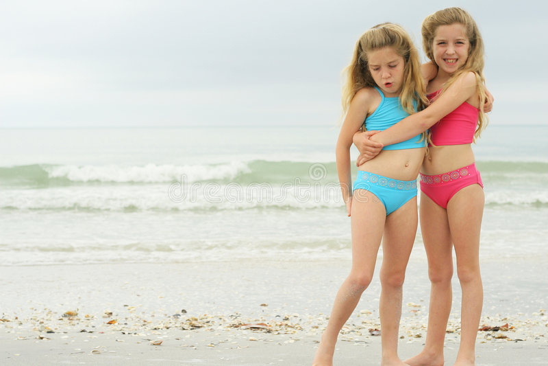 Girls hugging at the beach stock photo