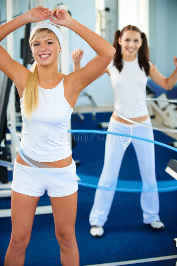 Girls with hula hoop. Portrait of two girls exercising with hula hoops in gym stock photos