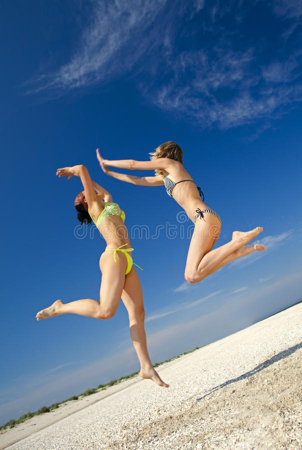 Girls jumping on a beach royalty free stock photo