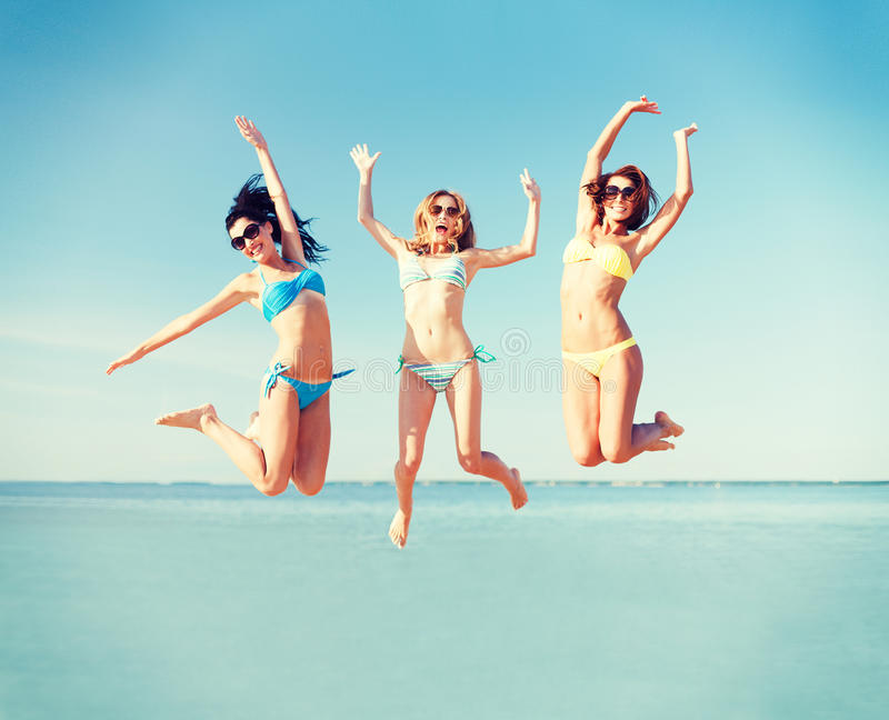 Girls jumping on the beach. Summer holidays and vacation - girls jumping on the beach stock photography