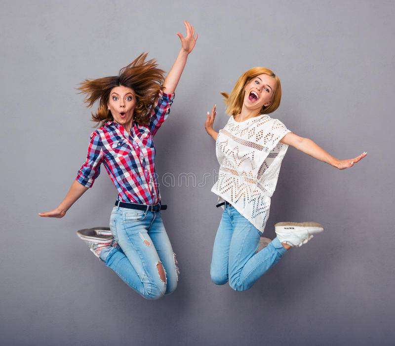Girls jumping over gray background stock photos