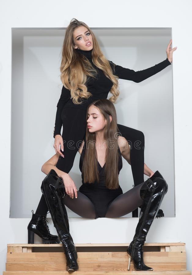 Girls just want to have fun. Ladies black bodysuits tights high heels looks bored. Friends in tight clothes bored invent royalty free stock photography