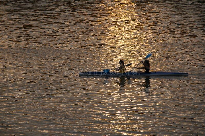 GIRLS KAYAKING AT SUNSET stock photo