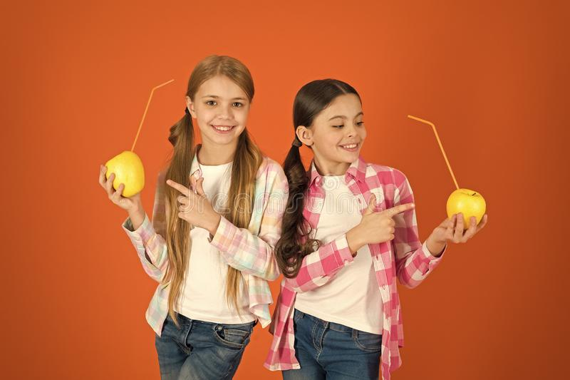 Girls kids casual style eat apple fruit orange background. Schoolgirls eat apple fruit. School lunch. Vitamin fruit. Nutrition for children. Healthy lifestyle royalty free stock image