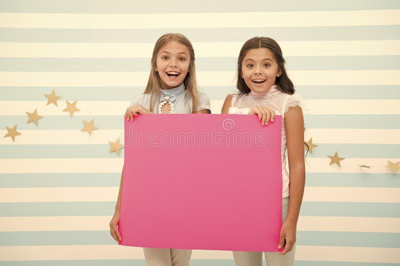 Girls kids hold advertisement poster copy space. Children hold advertising banner. Happy children with blank paper for. Advertisement. Advertisement concept stock photo