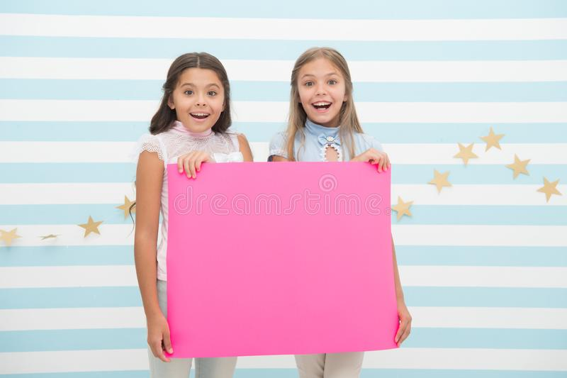 Girls kids hold advertisement poster copy space. Children hold advertising banner. Happy children with blank paper for stock image