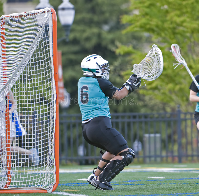 Girls lacrosse blocking the ball royalty free stock photography
