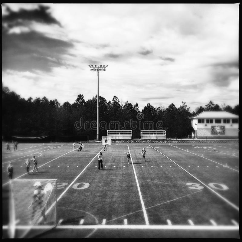 Girls lacrosse game. A black and white image of a lacrosse field with girls playing stock photo
