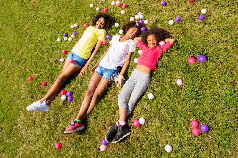 Girls lay in the grass and with color balls around. Group of black beautiful girls lay in the grass and with color balls around smile, view from above stock photography
